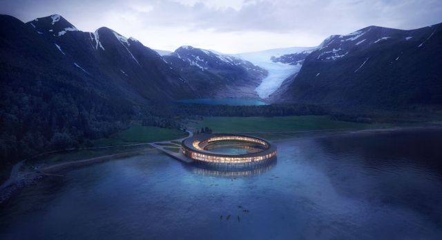 The new Snøhetta-designed hotel sits on stilts in the water by Svartisen in Nordland. Photo: Snøhetta/Plompmozes