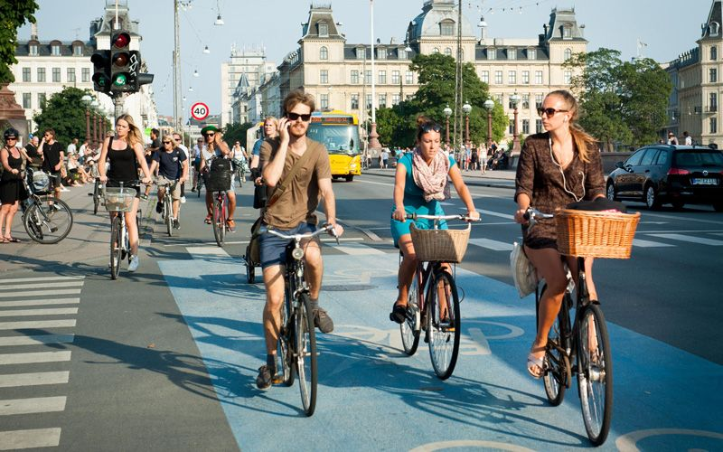 Young Danes riding bikes on cycle lanes around town on Dronning Louises Bro in sunny Copenhagen. Photo: Alamy Stock Photo