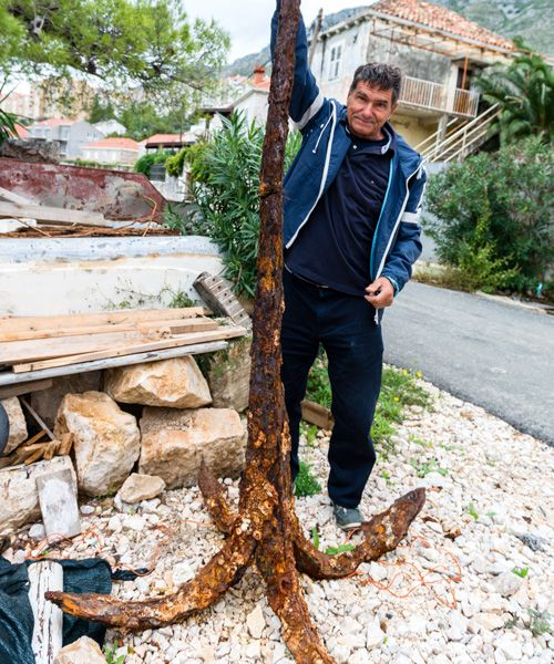 Jadran Gamulin in his backyard with an anchor from a shipwreck. Photo: Mauro Rongione