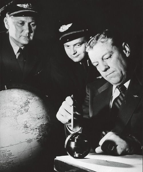 Navigators Erik Marcussen and Einar Sverre Pedersen study a gyro compass together with the manufacturer's representative D. Hembrough.
