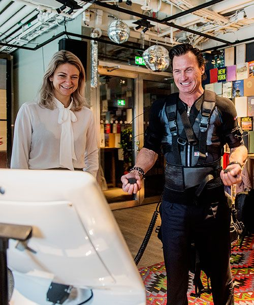 Lisa Farrar, CEO of eBerry, giving Stordalen a rundown on an electric muscle stimulator, a workout device which may be found at Nordic Choice hotels in the future. Photo: Magnus Liam Karlsson